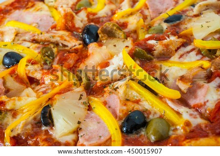 Hawaiian pizza with pineapple, ham, chicken, cheese, olives and vegetables - stock photo