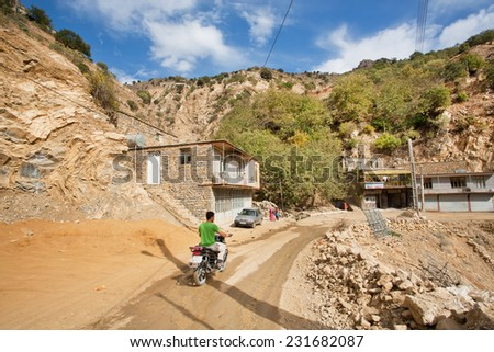 HAWRAMAN-E TAKHT, IRAN - OCT 10: Racer on motorcycle rides through the mountain village on dirt road on October 10, 2014 in Kurdistan. Islamic Republic of Iran is the world's 17th most populous nation - stock photo