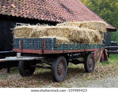 Hay wagon with stacked bales at a barn front - stock photo