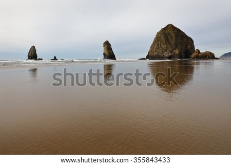 Haystack Rock, Cannon Beach, Oregon, USA. Afternoon at Haystack Rock in Cannon Beach, Oregon as the surf washes up onto the beach. United States.  - stock photo