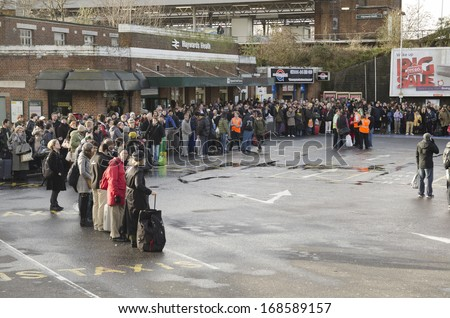 HAYWARDS HEATH, UK - DECEMBER 24th: People waiting / delayed at train station after the bad storm on December 24th, 2013. The storm caused many delays, stopping people getting home for Xmas. - stock photo