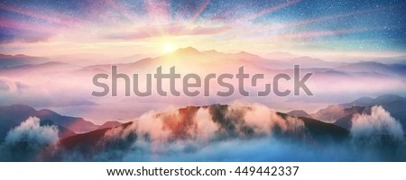 Haze under the stars in the fabulous mountains. Against the background of blue tops and peaks sea of fog after the rain in the Carpathians, beautiful valley lit glow of moonrise - stock photo