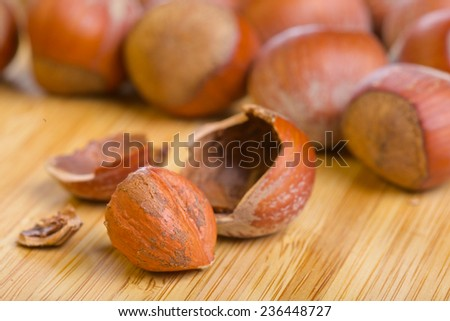Hazelnut or filbert kernel and its shell on old wooden background - stock photo