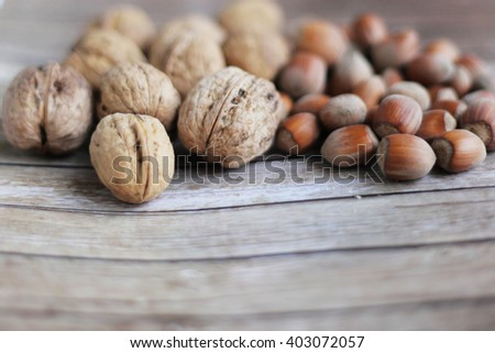 Hazelnuts and walnuts. Different nuts. Nuts on the wooden background.  - stock photo