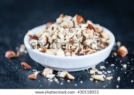 Hazelnuts (chopped, selective focus) on vintage background (close-up shot) - stock photo