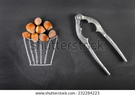 Hazelnuts, cracker and drawn bowl on blackboard with copy space. - stock photo