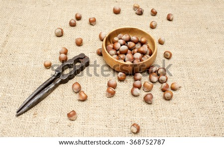 Hazelnuts in a wooden case on burlap with nutcracker.  - stock photo