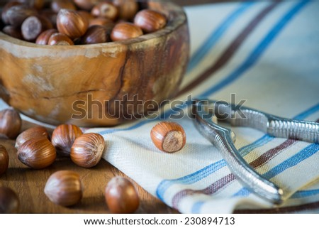 hazelnuts in bowl and nut cracker on cloth on table - stock photo