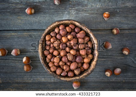 Hazelnuts in bowl on dark wooden background, top view, selective focus - stock photo