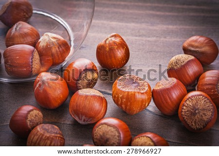 hazelnuts poured on vintage wooden board  - stock photo