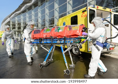 HAZMAT medical team pushing stretcher by ambulance on street - stock photo