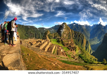 HDR image of tourists observing the wonder of Machu Picchu, the lost city of the Inca near Cusco, Peru.  - stock photo