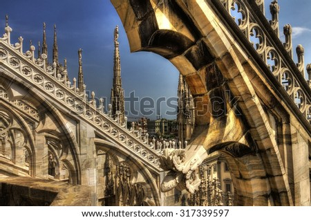 HDR photo of the white marble statues, spires and stone sculptures on the roof of famous Cathedral Duomo di Milano on piazza in Milan, Italy  - stock photo