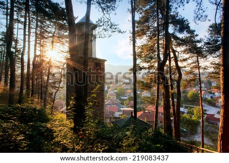 HDR sunset over the small mountain town in bulgaria, clock tower and forest in foreground  - stock photo