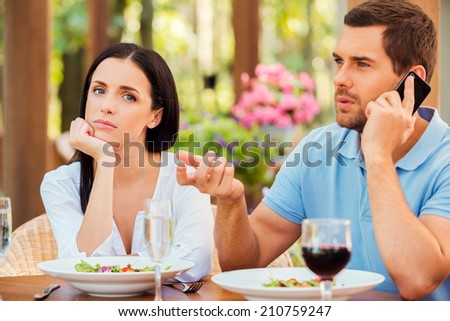 He always ignoring me. Depressed young woman holding hand on chin and looking at camera while her boyfriend talking on the mobile phone at outdoors restaurant - stock photo