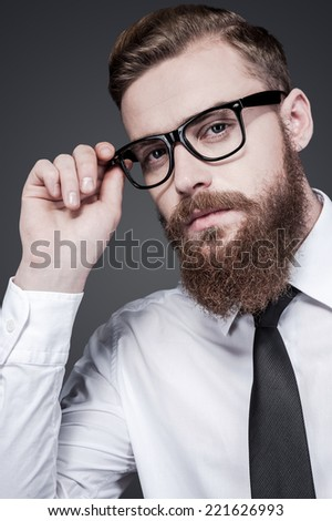 He got creative mind. Handsome young bearded man in shirt and tie adjusting his eyeglasses and looking at camera while standing against grey background - stock photo