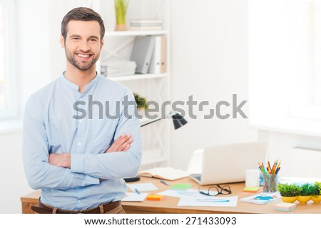 He got creative mind. Handsome young man in shirt keeping arms crossed and smiling at camera while leaning at the desk in office - stock photo