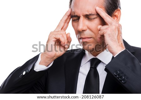 He got stressful job. Frustrated mature man in formalwear touching head with fingers and keeping eyes closed while standing against grey background - stock photo