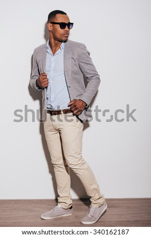 He got trendy look. Confident young African man in smart casual clothing looking over shoulder while standing against white background - stock photo