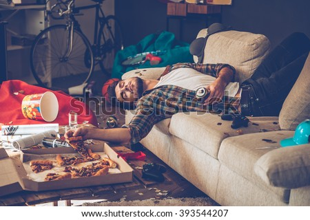 He had too much beer. Young handsome man passed out on sofa with pizza slice and beer can in his hand in messy room after party - stock photo