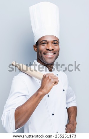 He is a champion in the kitchen. Cheerful young African chef in white uniform carrying rolling pin on his shoulder while standing against grey background - stock photo