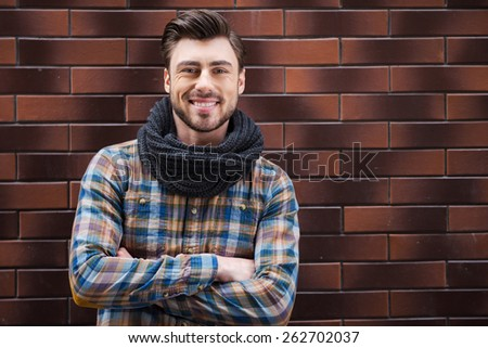 He is a stylish guy. Handsome young man leaning the wall and looking at camera while standing against brick wall - stock photo
