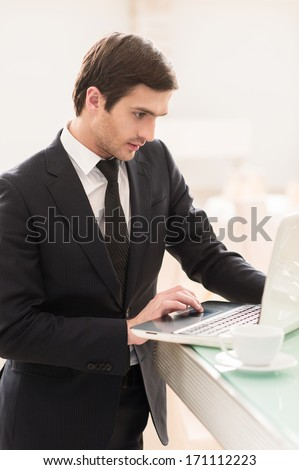 He is always connected. Confident young man in formalwear using his laptop while standing at the bar  - stock photo