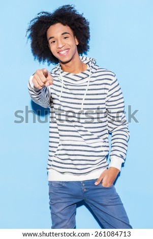He is choosing your smile! Handsome young African man pointing in to the camera while standing against blue background  - stock photo