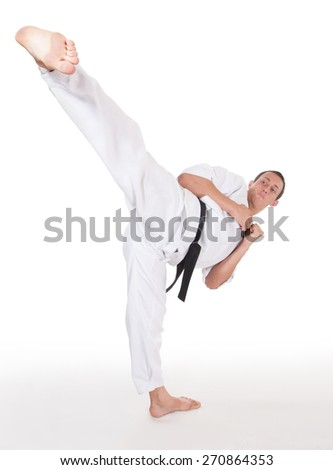 He is fighter. Young man show foot kick in head on white. - stock photo