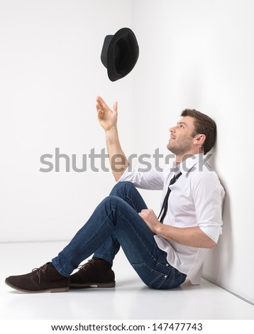 He is full of new ideas. Happy young funky men throwing his hat up while leaning on the wall - stock photo