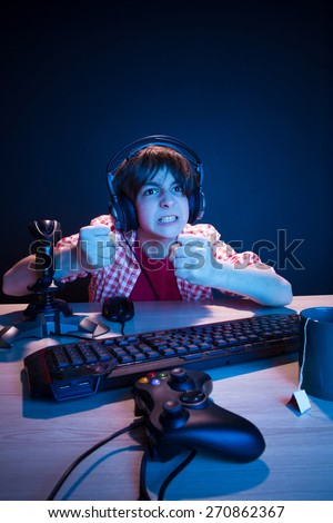He is going to revenge to another player. He like play and win video games. In blue light of display emotional kid play computer games online. - stock photo