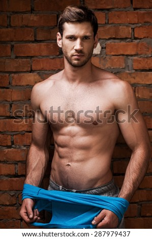 He is in a good shape. Serious young muscular man taking off his tank top while standing against brick wall  - stock photo