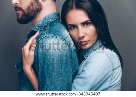 He is my everything. Side view of beautiful young woman bonding to back of beard man and looking at camera while both standing against grey background  - stock photo