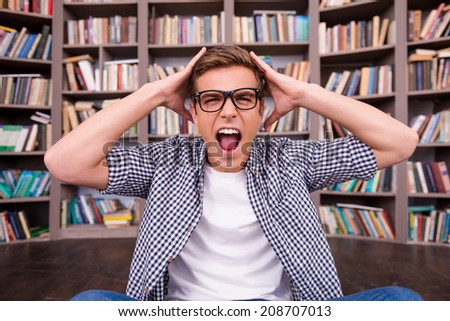 He is not ready to final exams. Shocked young man touching his head with hands and shouting while sitting against bookshelf - stock photo