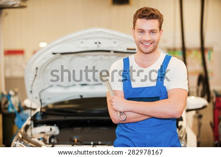He is ready to work. Confident young man in uniform holding a wrench an smiling while standing in workshop with car in the background - stock photo