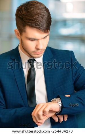 He knows that time is money. Serious young business man in formalwear checking time and looking at his watch while sitting in the hall of the airport - stock photo