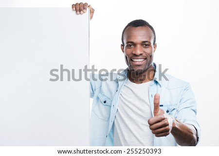 He knows what is good! Handsome young black man gesturing and leaning at the copy space  while standing against white background  - stock photo