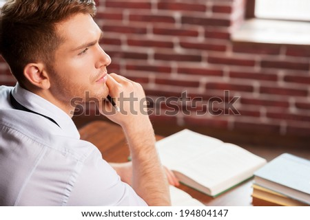 He needs some fresh ideas. Top view of handsome young man in shirt and tie holding hand on chin and looking away while sitting at his working place  - stock photo