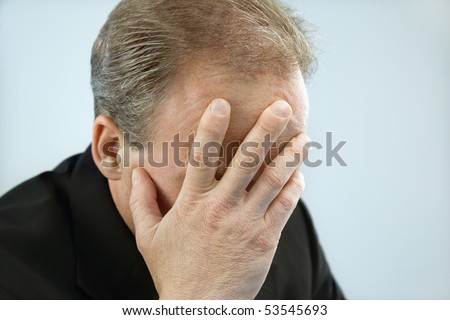 Head and shoulder portrait of middle aged  Caucasian businessman covering face with hand. - stock photo