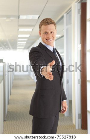 Head and shoulder portrait of young businessman with handshake - stock photo