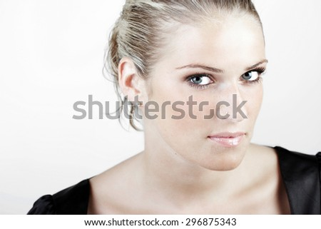 Head and Shoulder Shot of a Gorgeous Young Blond Woman Looking Fierce at the Camera Against White Background. - stock photo