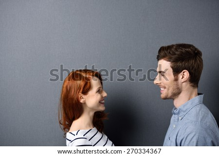 Head and Shoulder Shot of a Happy Young Couple Facing Each Other on a Gray Wall Background, Emphasizing Copy Space. - stock photo