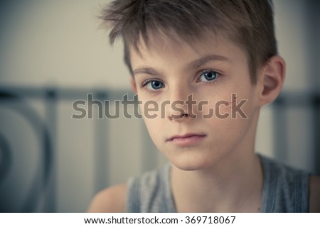 Head and Shoulder Shot of a Serious Young Boy with Small Scars on his Face, Staring Straight at the Camera. - stock photo
