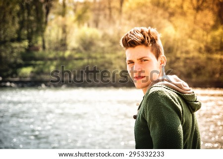 Head and shoulders length of contemplative light brown haired teenage boy wearing green hooded-shirt beside picturesque river or lake, looking at camera - stock photo