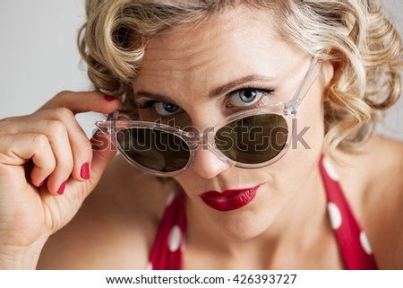 Head and shoulders portrait of a beautiful mid 30s woman dressed with retro vintage hair and makeup peeking behind sunglasses - stock photo