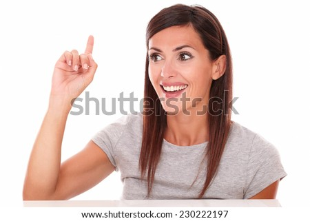 Head and shoulders portrait of friendly girl pointing up and looking to her right on isolated white background - copyspace - stock photo