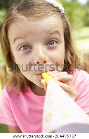 Head And Shoulders Portrait Of Girl Blowing Party Hooter - stock photo