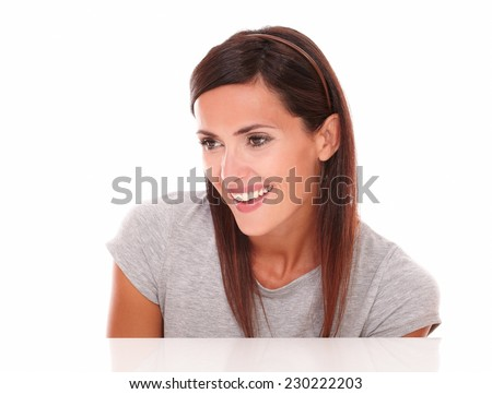 Head and shoulders portrait of happy latin female looking to her right down and smiling on isolated studio - copyspace - stock photo