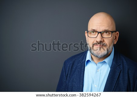 Head and Shoulders Portrait of Mature Man with Facial Hair Wearing Eyeglasses and Denim Jacket Looking Up with Wrinkled Forehead in Studio with Dark Gray Background and Copy Space - stock photo