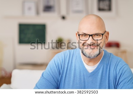 Head and Shoulders Portrait of Mature Man with Gray Facial Hair Wearing Eyeglasses and Casual Blue Shirt Smiling at Camera in Living Room on Relaxing Day at Home, Copy Space to Left of Image - stock photo